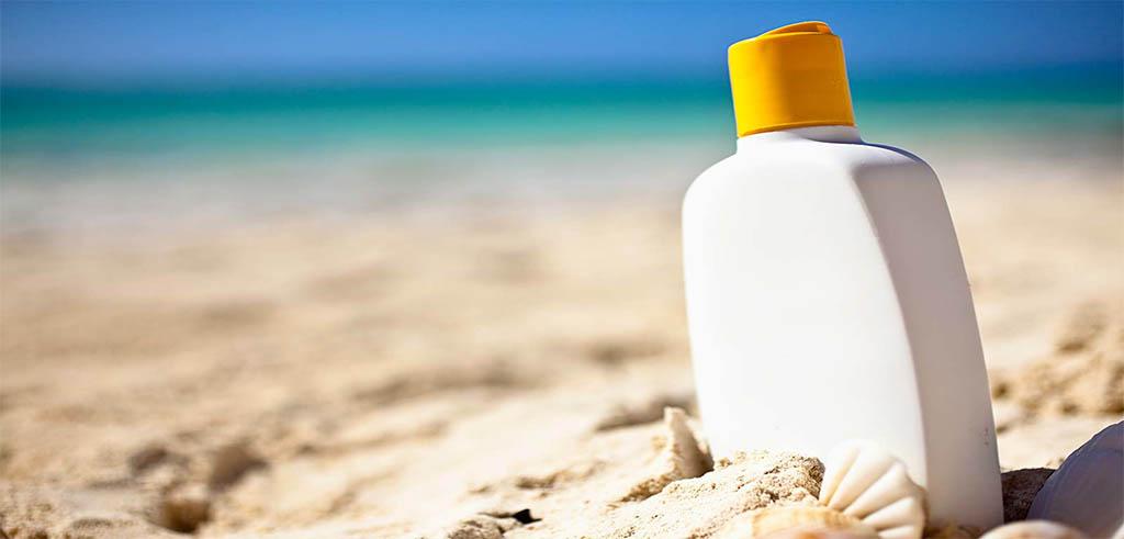 crema solar encima de la arena de la playa
