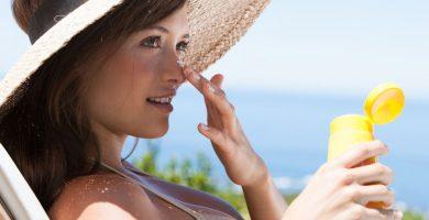 mujer en la playa usando proteccion solar en el rostro